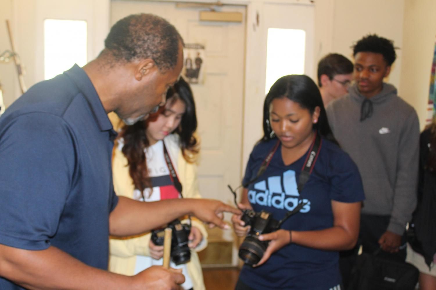 Mr. Lark demonstrates camera settings for students, Jasmine Stone and Carolyn Doan.
