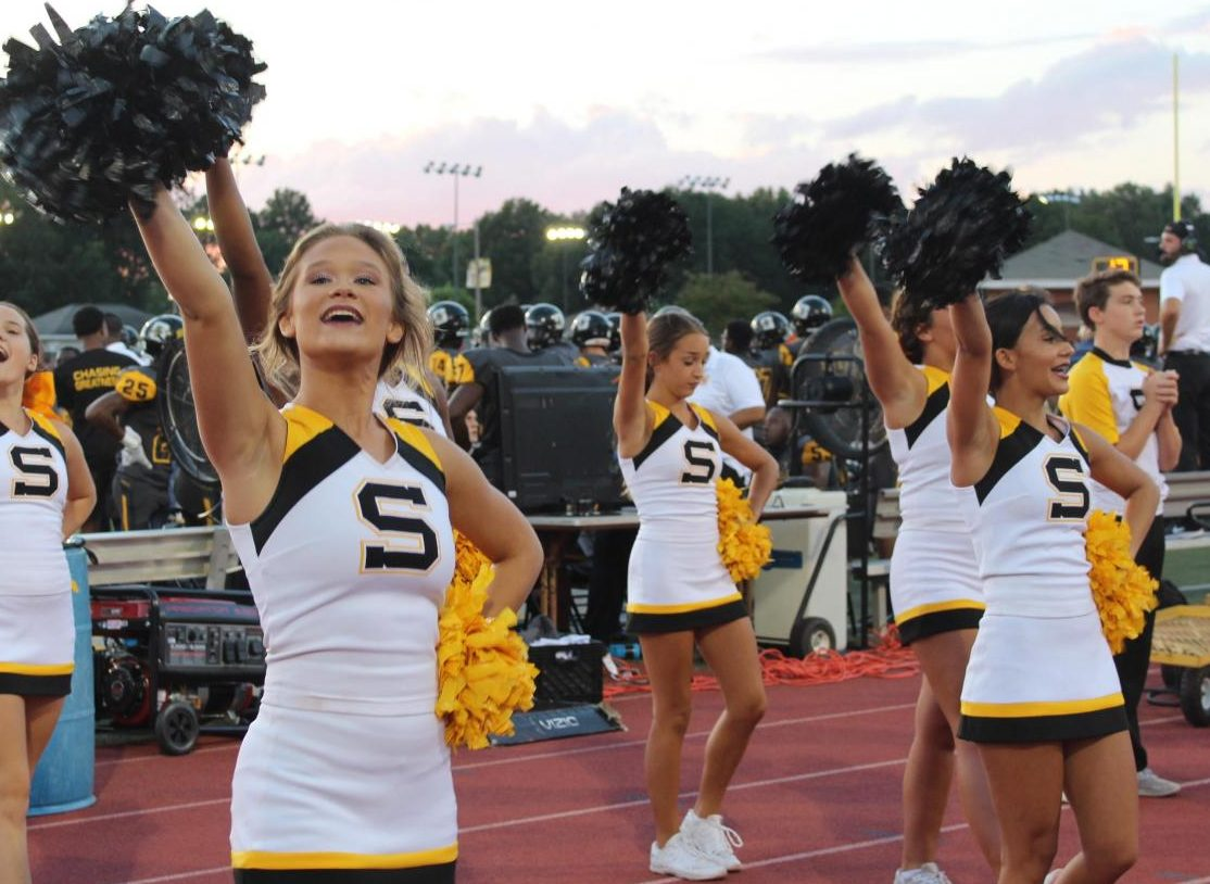 Cheerleaders cheer during a football game.
